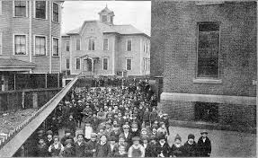 The school was completed at a cost of $57,000. This photo shows children next to the school, and the Africa Street school(built in 1881) in the distance.