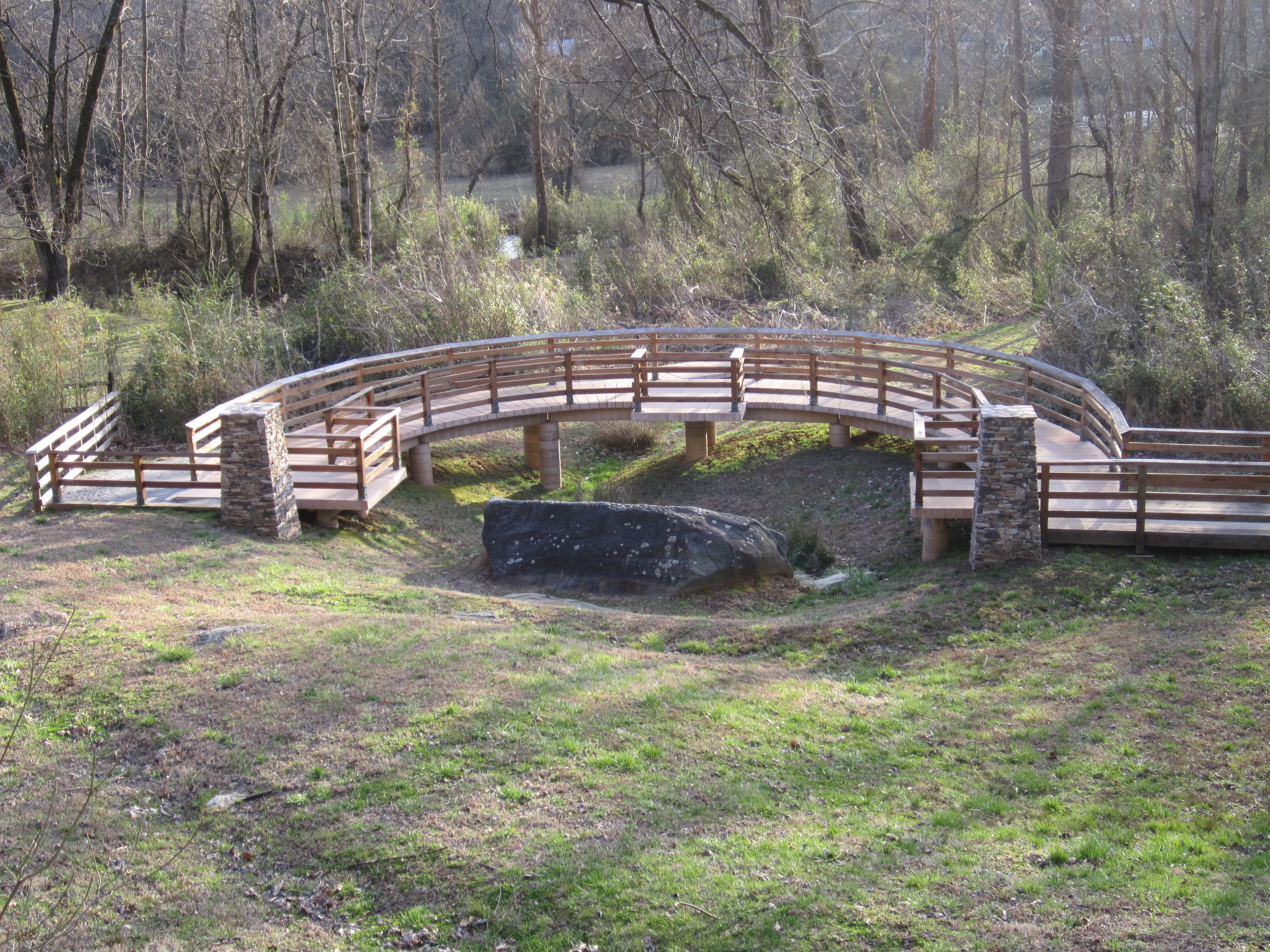 The site features a wooden walkway around the rock