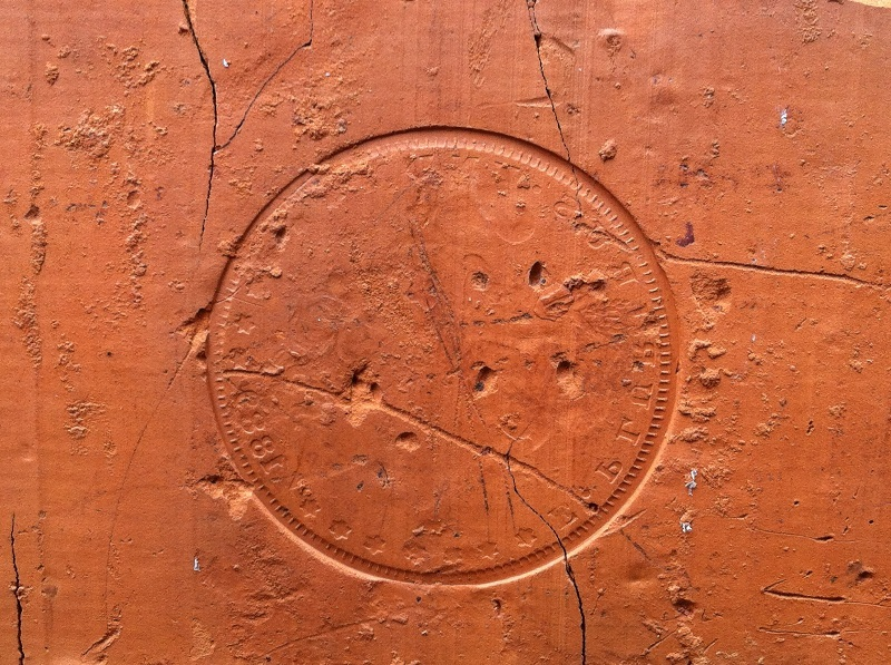 The impression of an 1889 coin on the building's exterior.