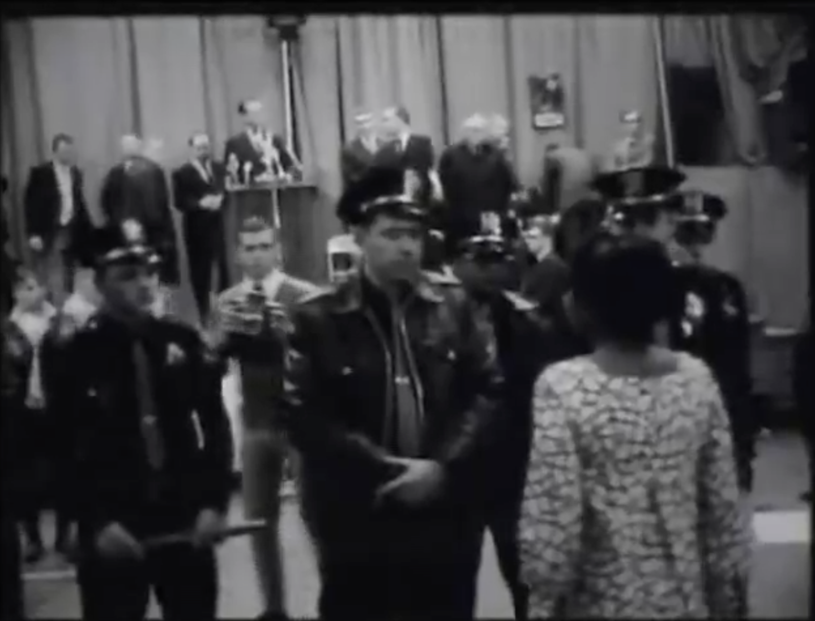 A protestor stands in front of several armed police officers protecting Alabama Governor George Wallace during a speech in Omaha, NE.