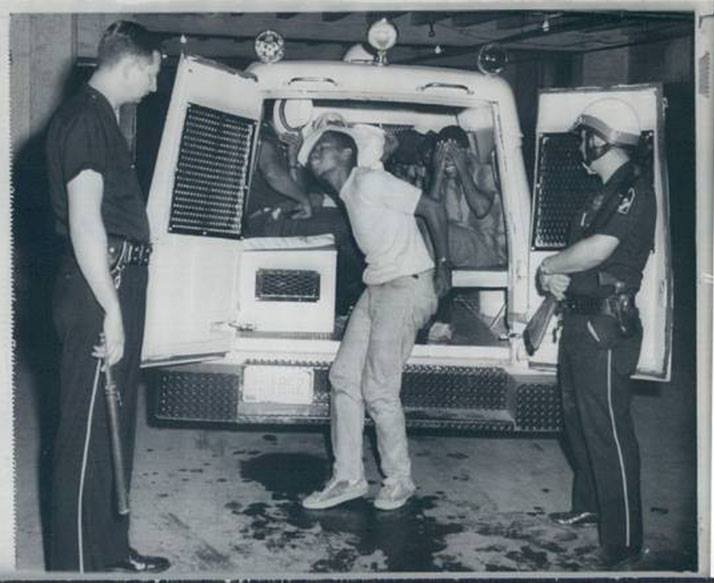 In this photo, black youth who were involved in the the 1 August, 1966 riot are being arrested and taken into custody.