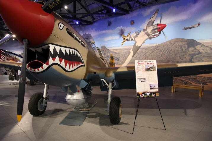 A fighter plane on display in font of a mural depicting in the sky