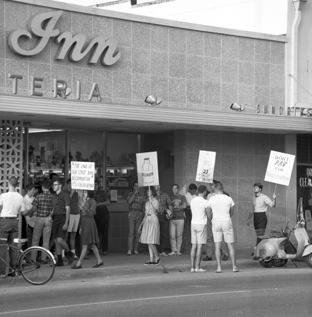 High school and college students, together with community members, lead a protest against segregation at the College Inn.