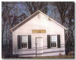 Front view of the one-room schoolhouse, which has been restored and operates as a museum.