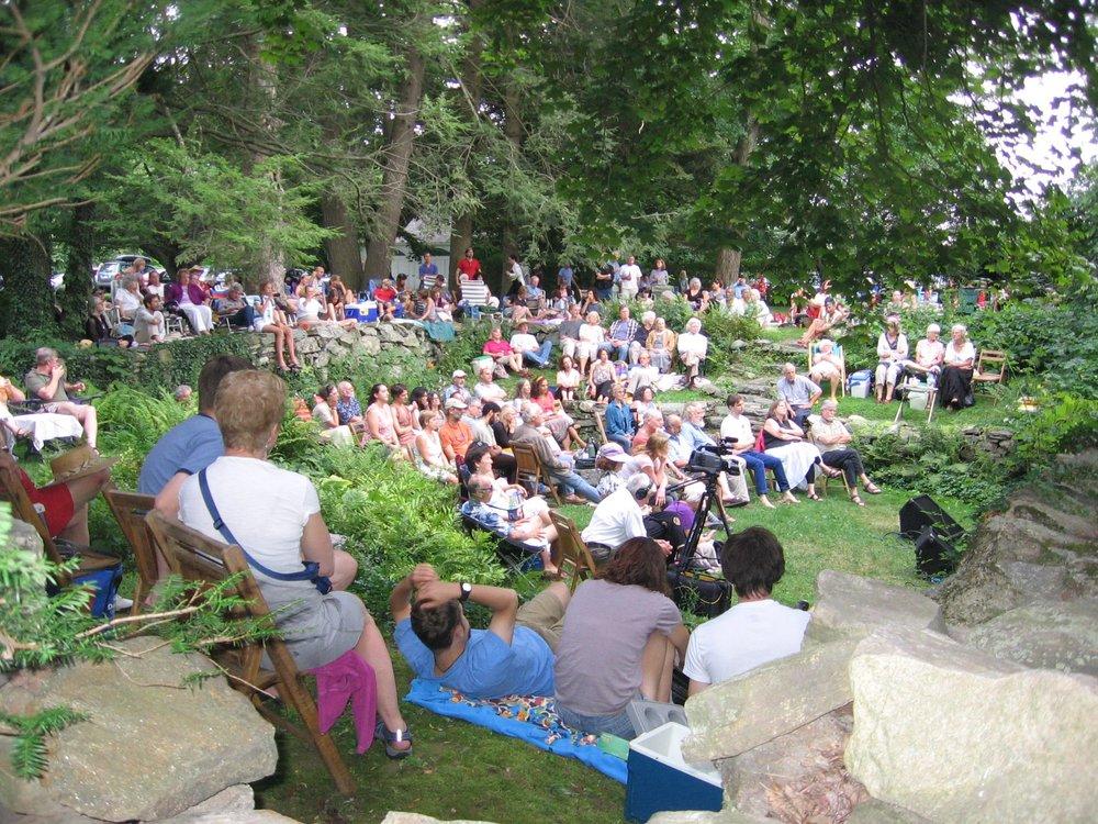 People enjoying a folk tradition concert in the house's sunken garden.