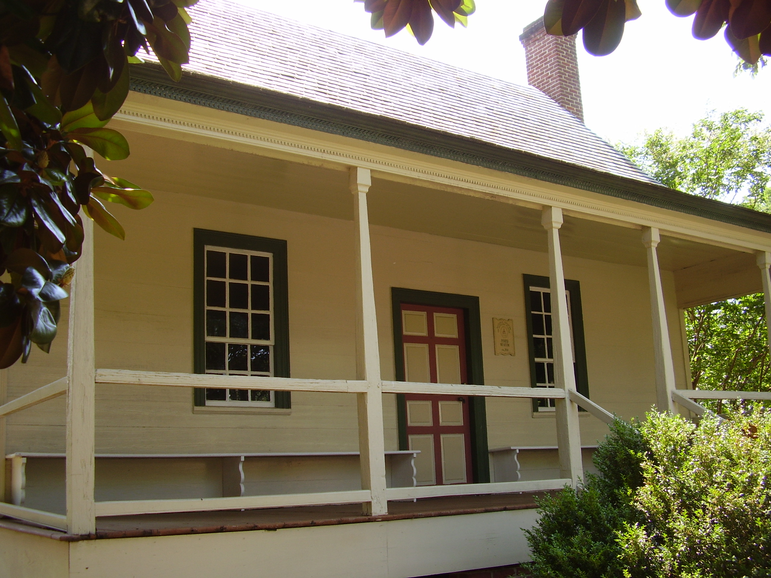 The front entry of the house features original porch posts and benches on the front porch which served as a work area for some activities such as shelling beans or shucking corn.