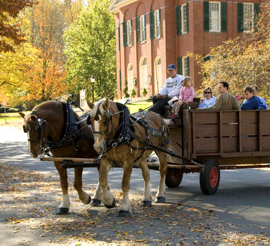 Visitors enjoy a horse-drawn wagon ride through the village.