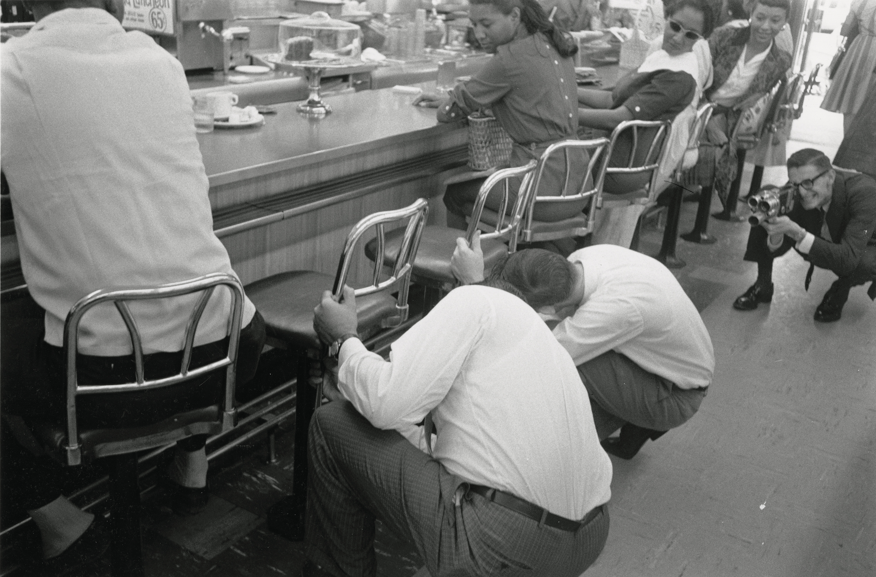 Staff remove stools during sit-in at White's Pharmacy. 
