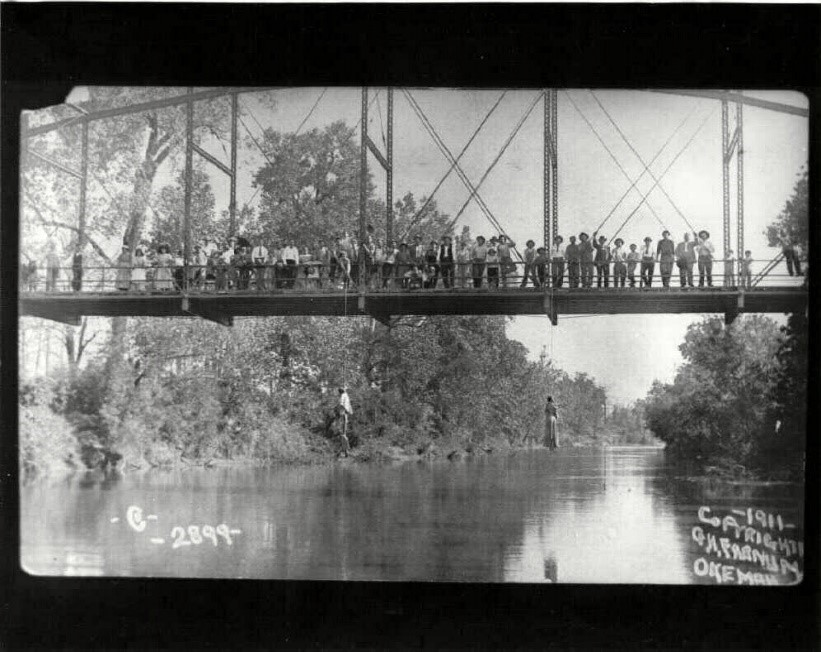 Photograph of Laura and L.D. Nelson along with lynch mob and observers on the Schoolton Bridge after the lynching.