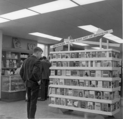 """Student looking at book display in Alliot bookstore"", 1970s"