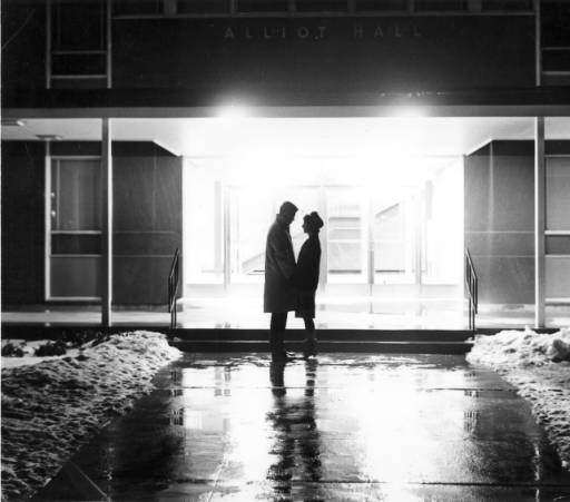 """Male and female in silhouette holding hands and looking at one another outside a lit up entrance to Alliot"", 1960s"