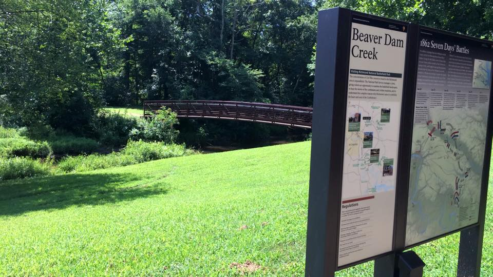 An interpretive sign with the bridge over Beaver Dam Creek in the background.
