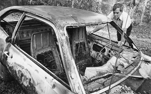 The controversy quickly escalated. Textbook protester Donald Means examines his burned car.