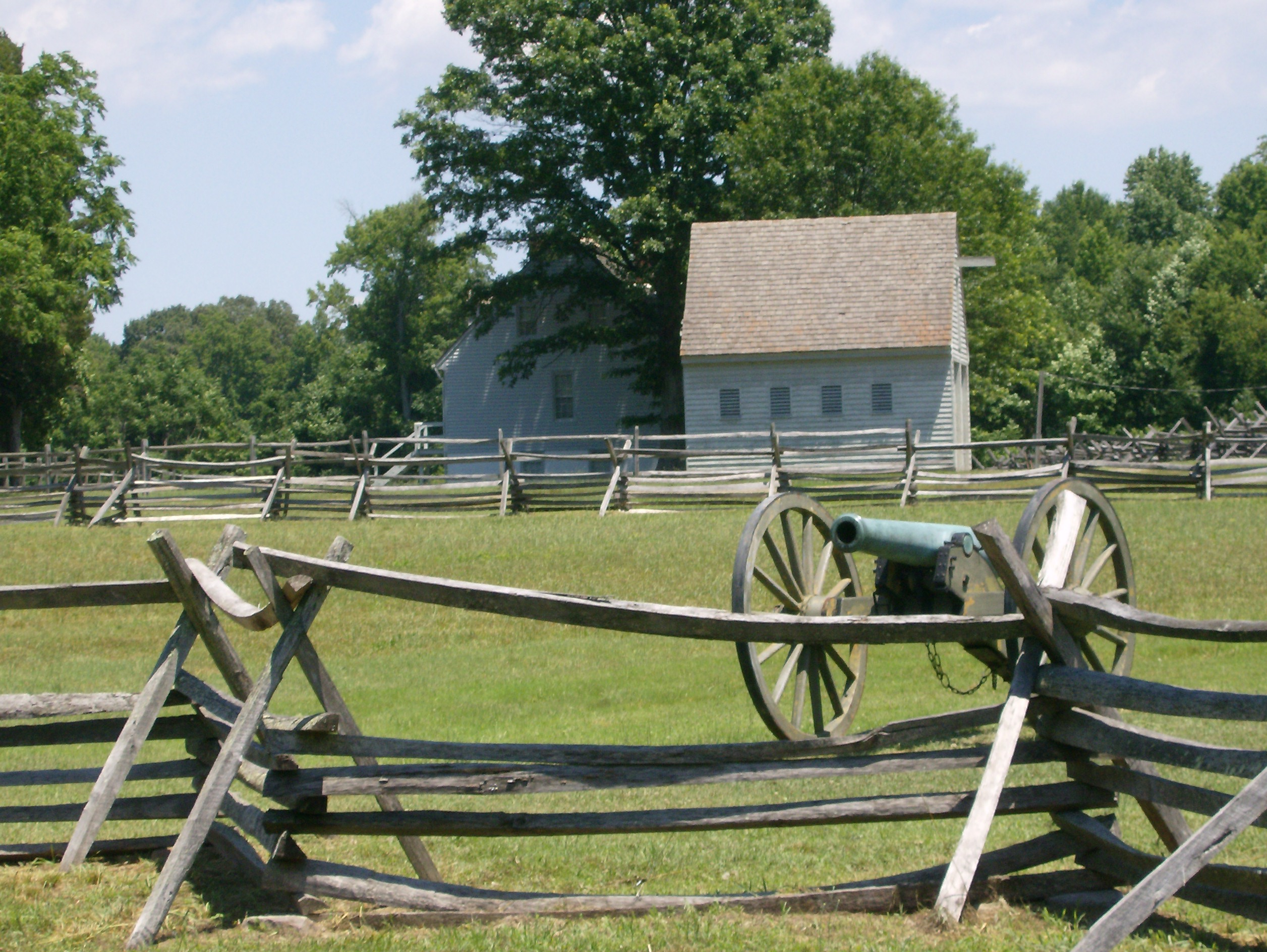 A cannon and the Watt House overlook the battlefield.