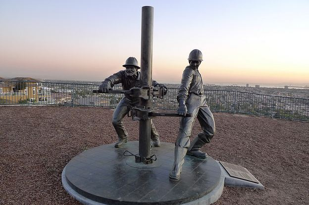 "This photo shows a sculpture created by Cindy Jackson titled ""Tribute to the Roughnecks"" depicting two men bringing up petroleum following the 1921 oilfield discovery."