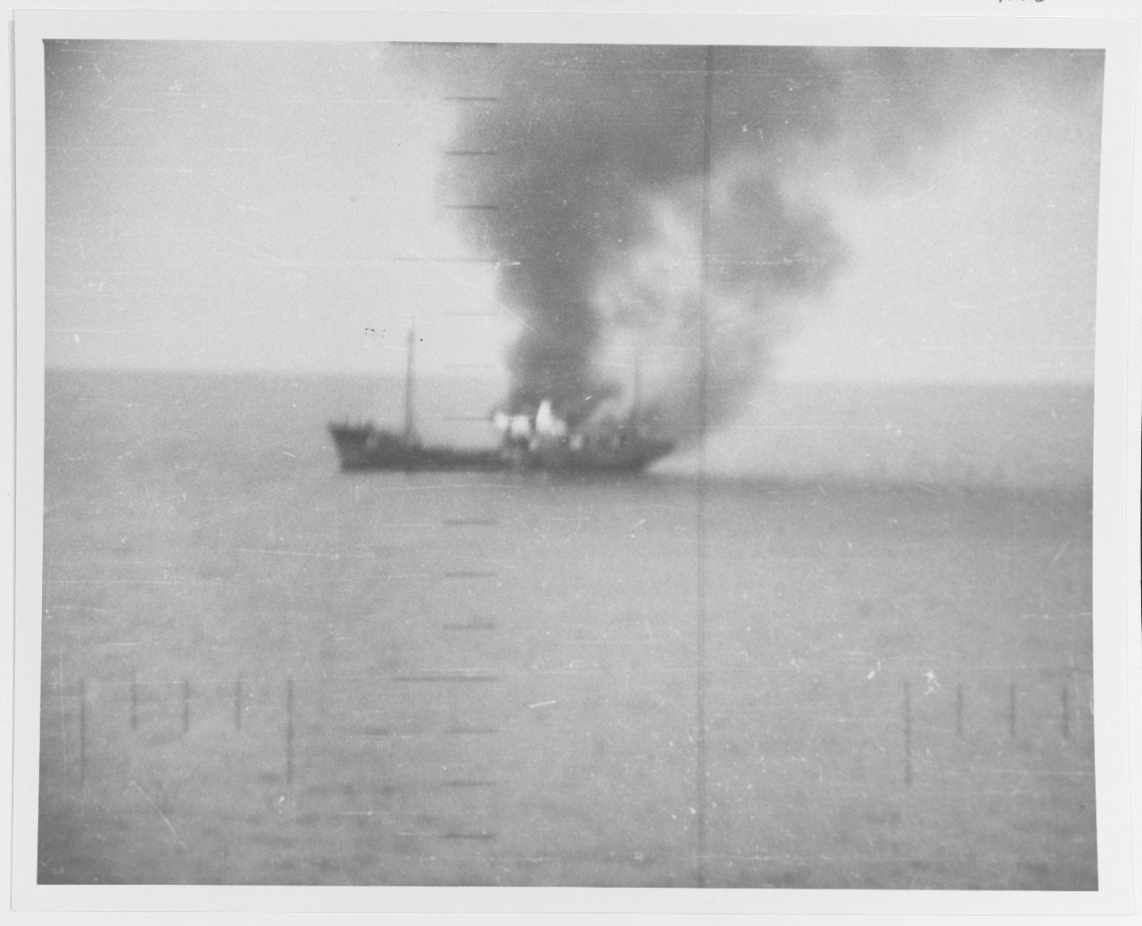 A Japanese picket vessel engulfed in flames after being attacked by the Silversides in October 1942. This photograph was taken through the sub's periscope. National Archives, RG80.