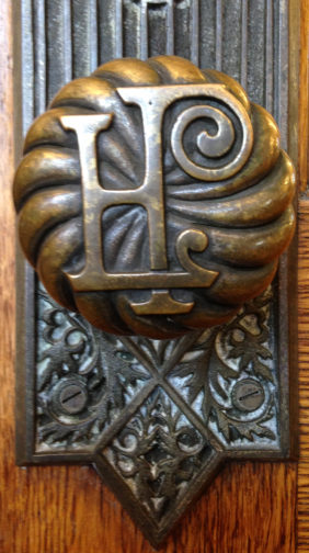 "Detail of a doorknob with the library logo ""HPL"""