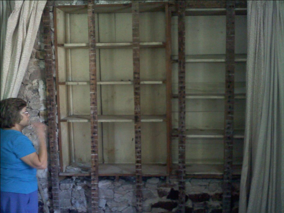 Margaret Choate showing what we believe is the c1721 outside wall of the original cabin.  Margaret is standing in the section of the house added in 1810 by the Penroses