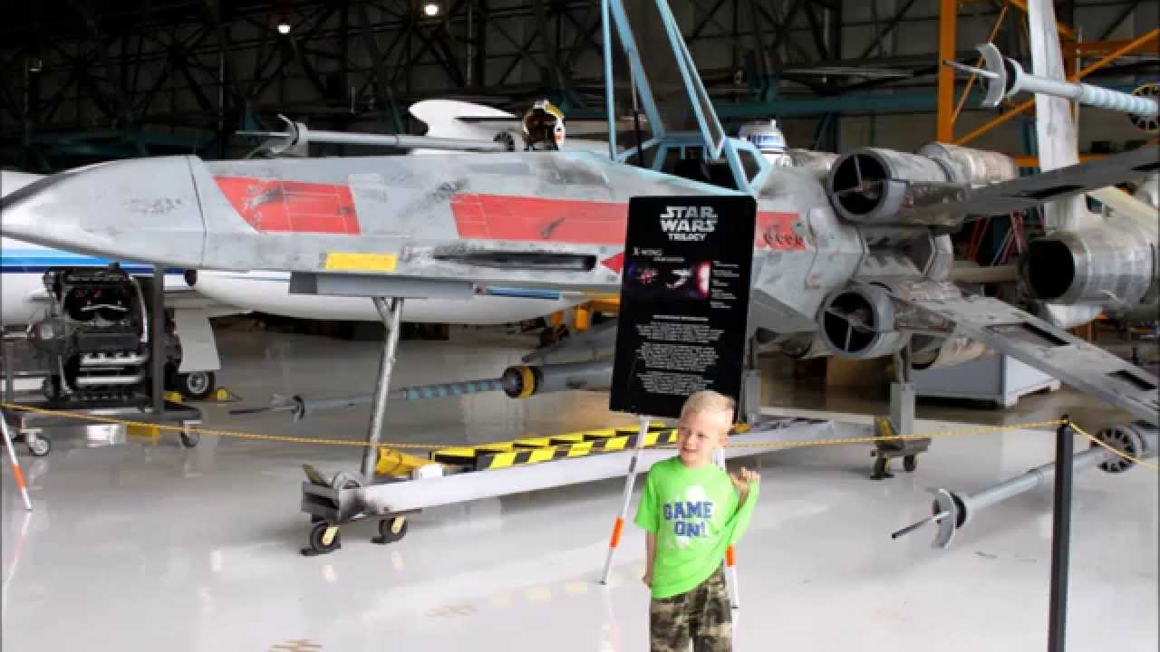 A future x-wing pilot in front of his x-wing fighter.