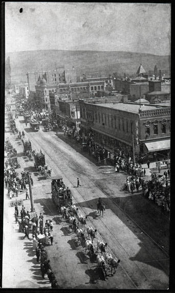 Electric streetcars traveling down Higgins Ave along side horse-drawn carriages, circa 1915