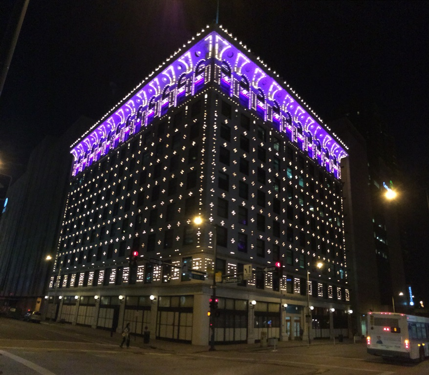The Denver Gas and Electric Building lit up at night.