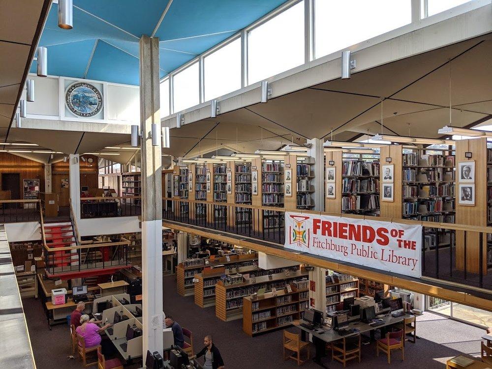 View of library book shelves, atrium and ceiling, with arched supports