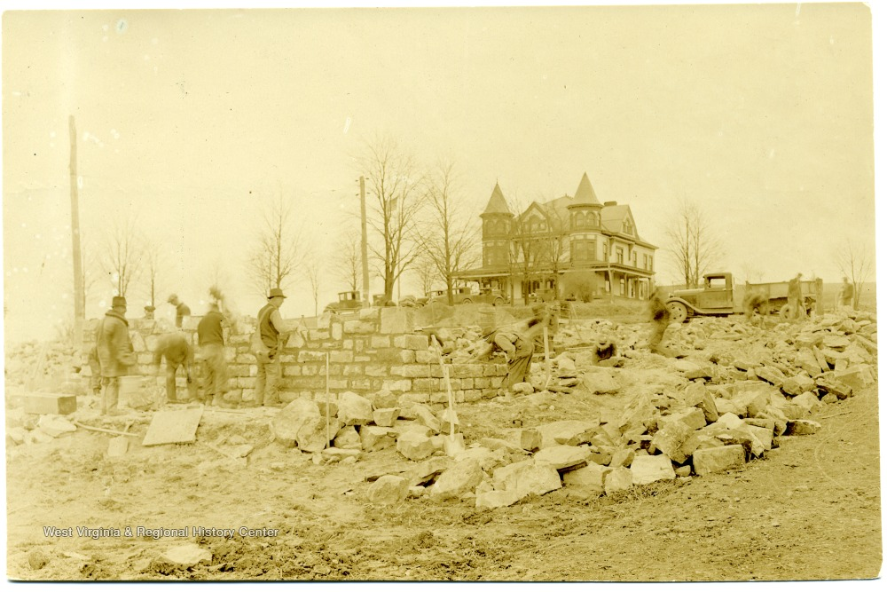 Builders setting the foundation of Admin - note Arthur Mansion behind it