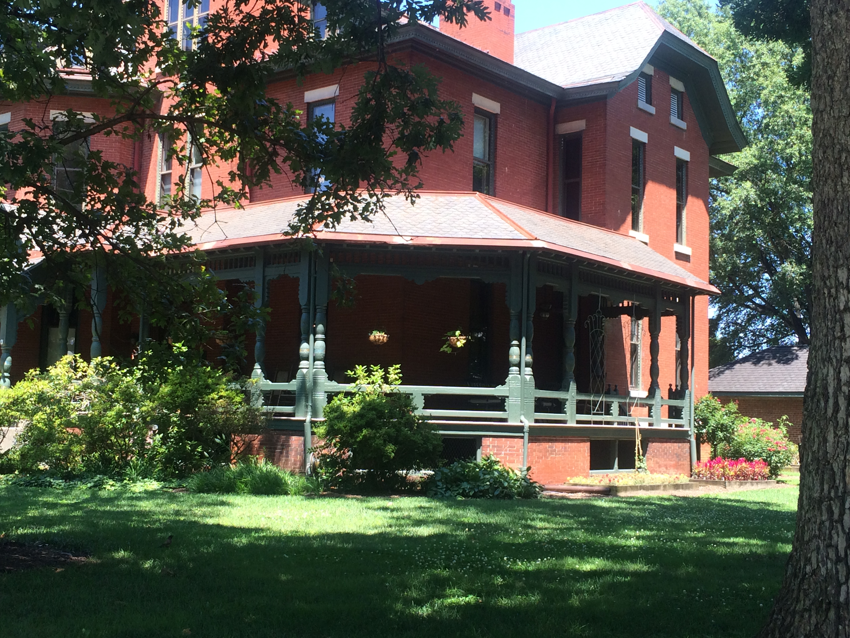 A view of the southern facade taken from an angle. This view showcases the verandah and some of the landscaping.