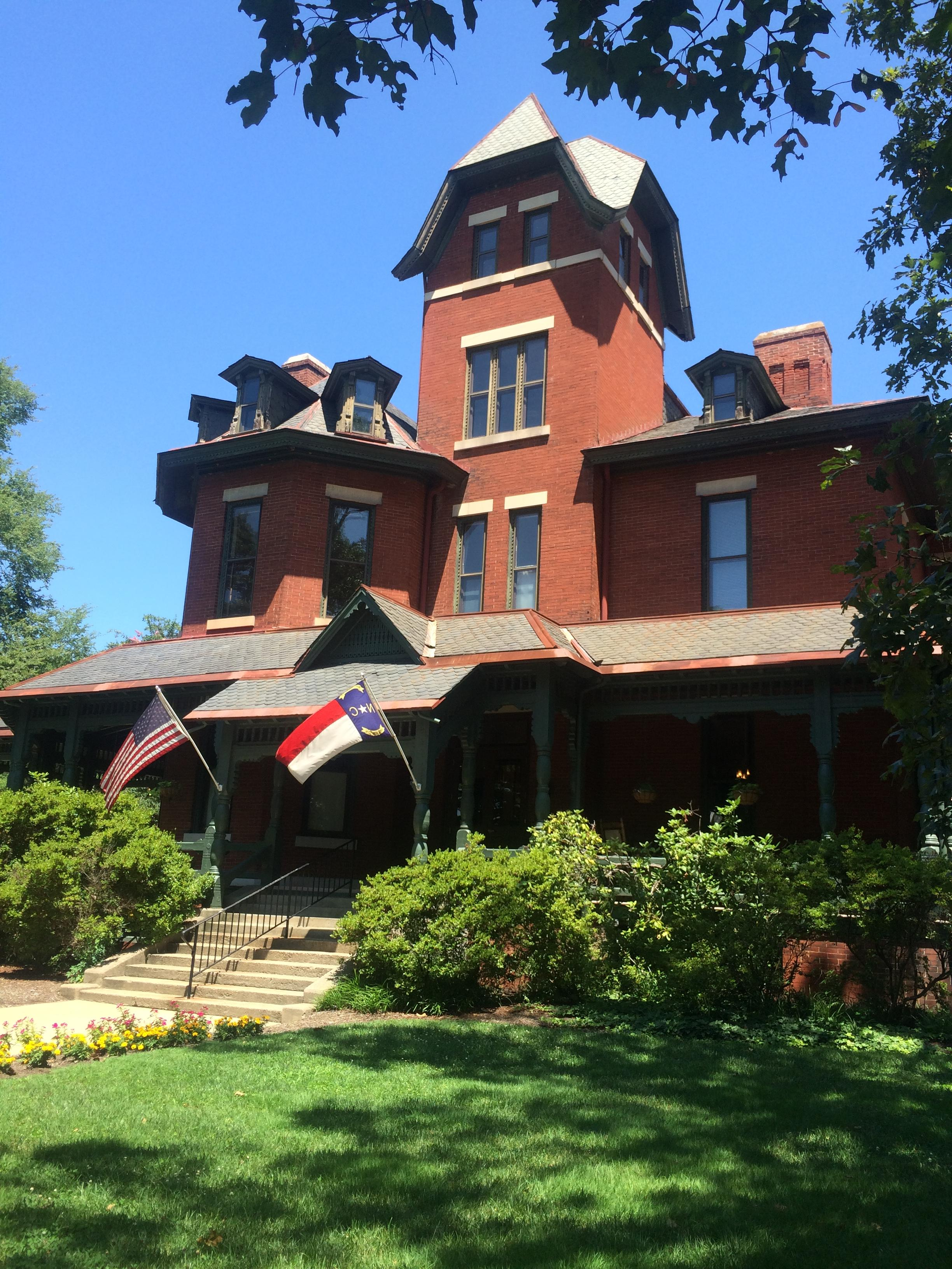 Another view of the front, western facade taken at an angle. US and North Carolina flags waving in the summer breeze.