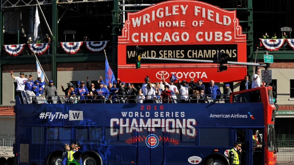 The Chicago Cubs celebrating during their World Series parade outside of Wrigley Field.