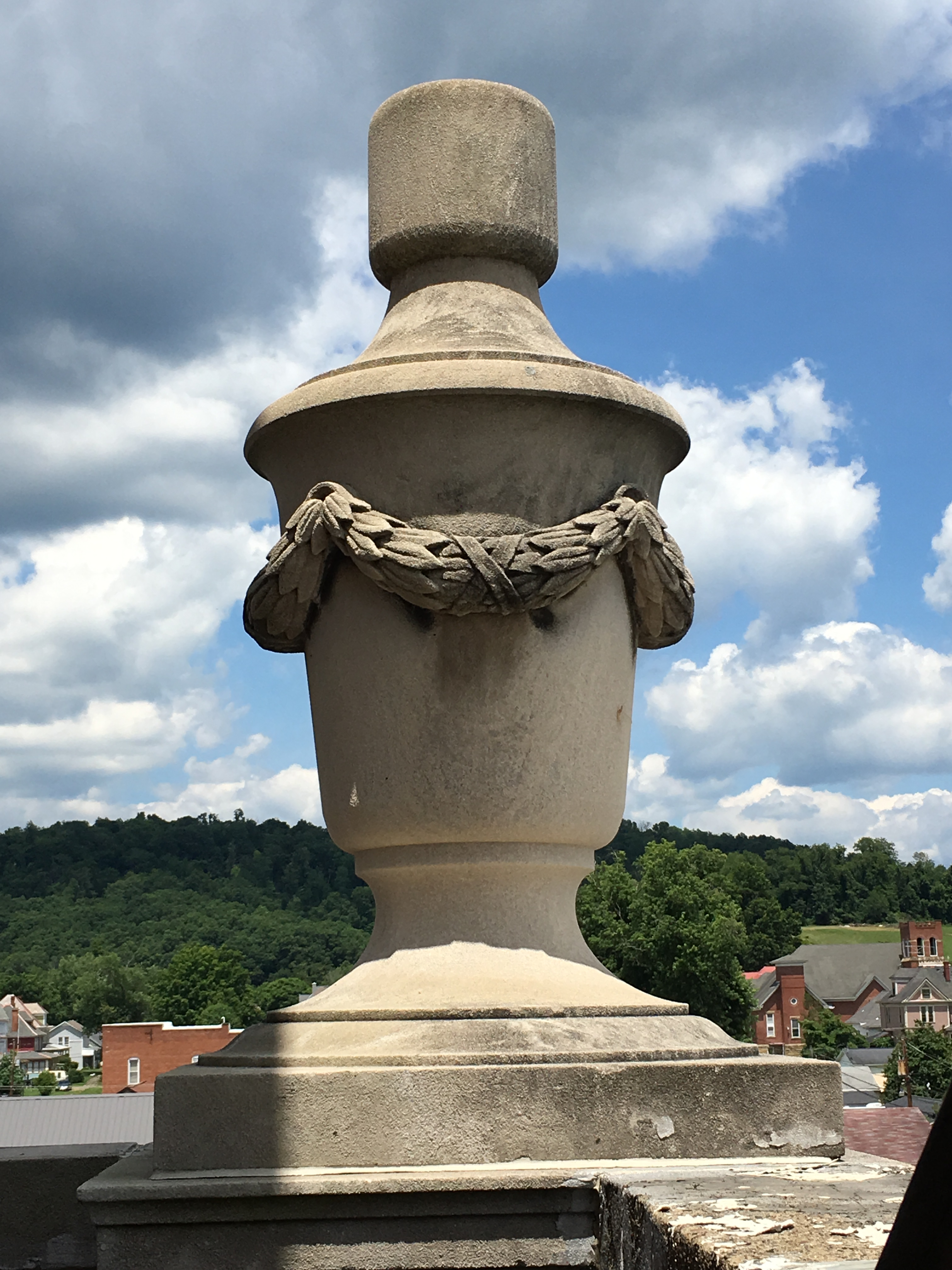 Four urns adorn the four-cornered ledge just below the bell tower. 