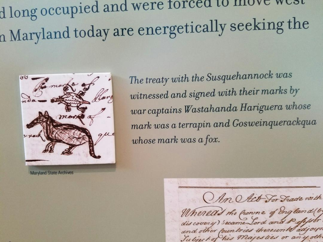 Information board in St. John's Museum in St. Mary's City. About the Native America's signing documents with the officials of the town. 