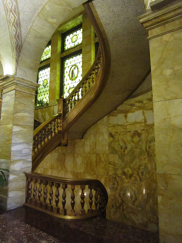 The interior of the Equitable Building features imported marble, brass railings, stained glass windows, and mosaic ceilings with Byzantine motifs. Photo by Christine Franck. Licensed under Creative Commons,