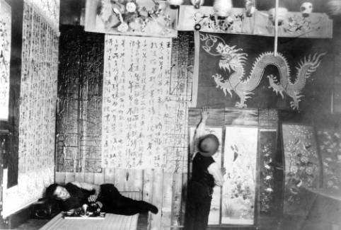 A photograph taken before1912 shows one resident of Denver's Chinatown decorating for the Chinese New Year while another smokes a water pipe. Denver's Chinese population slowly dwindled in the early decades of the century.