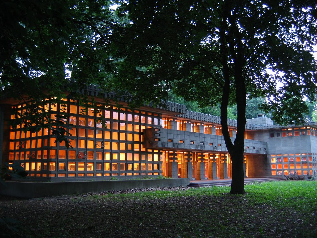 Lights on inside at dusk showcase the home's unique block windows