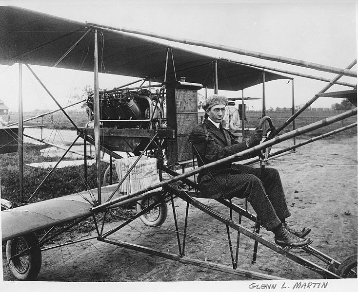 C. 1912, Glen L. Martin in a pusher bi-plane. Note the newspapers. Martin delivered papers in California as a promotional stunt.