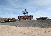 Apache Attack Helicopter and Two M1 Abrams Tanks are located right outside the main gate.