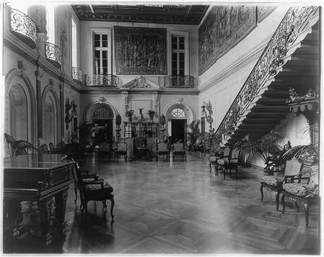 The lavish ballroom of the Anderson house, which includes ornate iron balconies and a staircase, tapestries, and decorative furniture. Courtesy of the Library of Congress.