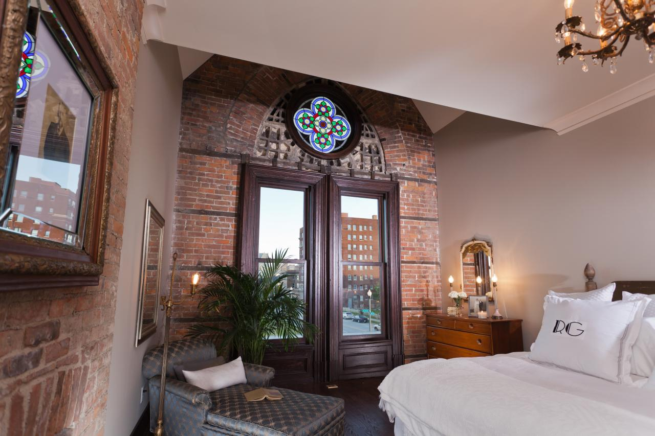The master bedroom after renovation, with a stained glass window and a photo of Ransom Gillis over the fireplace