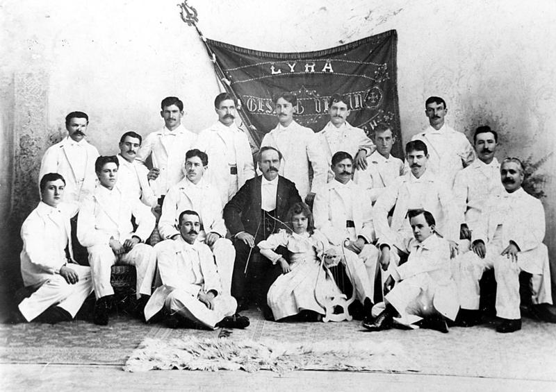 The Lyra Men's Choir, directed by Reuben Kempf with his daughter Elsa as mascot (center)
