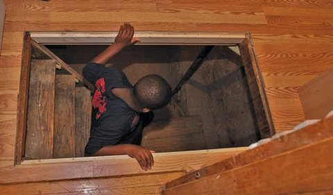 On the Underground Railroad Tour, a boy investigates a small room below a trap door, believed to house fugitive slaves