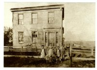 A historical photo of the Kellogg-Warden house when it was in Lower Town, with the Greiner family standing in front. The Greiners owned the home for 100 years.