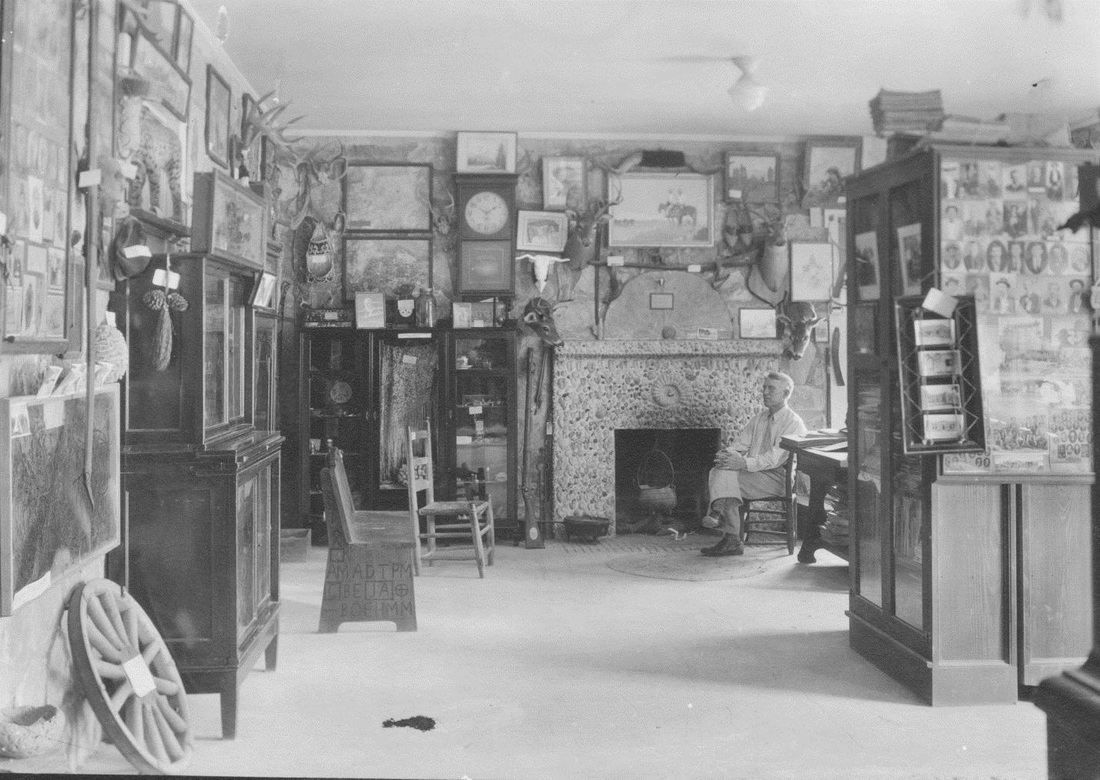 The Frontier Times Museum founder John Marvin Hunter sitting in the museum's gallery of curiosities, circa 1935.