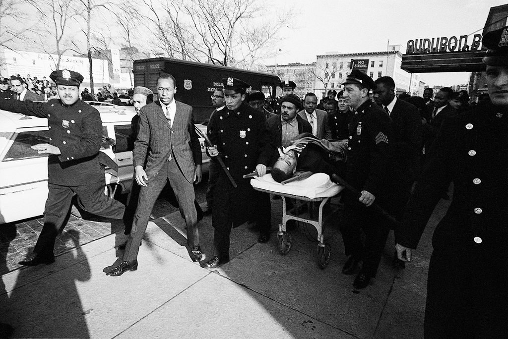 Mortally wounded, Malcolm X is carried from the Audubon Ballroom to a nearby hospital
