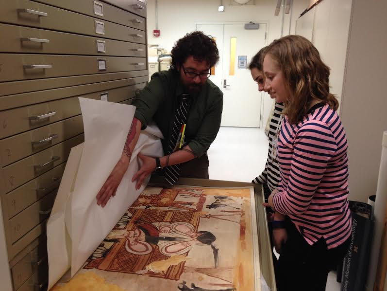 A curator shows students a reproduction print in the museum's collections