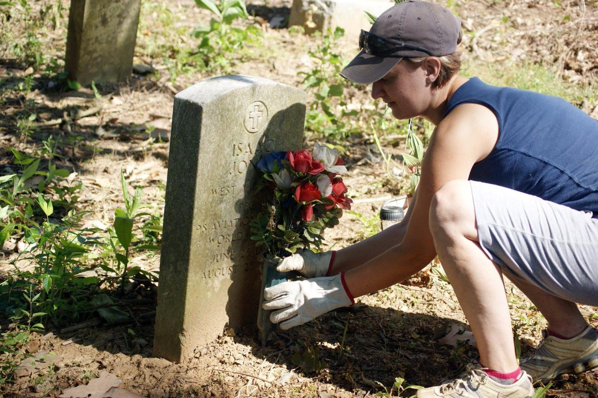 Huntington resident, Leigh Anne Shelton places flowers at the grave of WWI veteran Isaac Jones during cleanup efforts in 2013