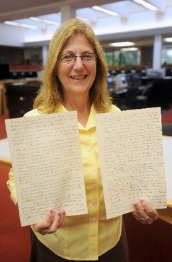 An archivist holds up original copies of university archives
