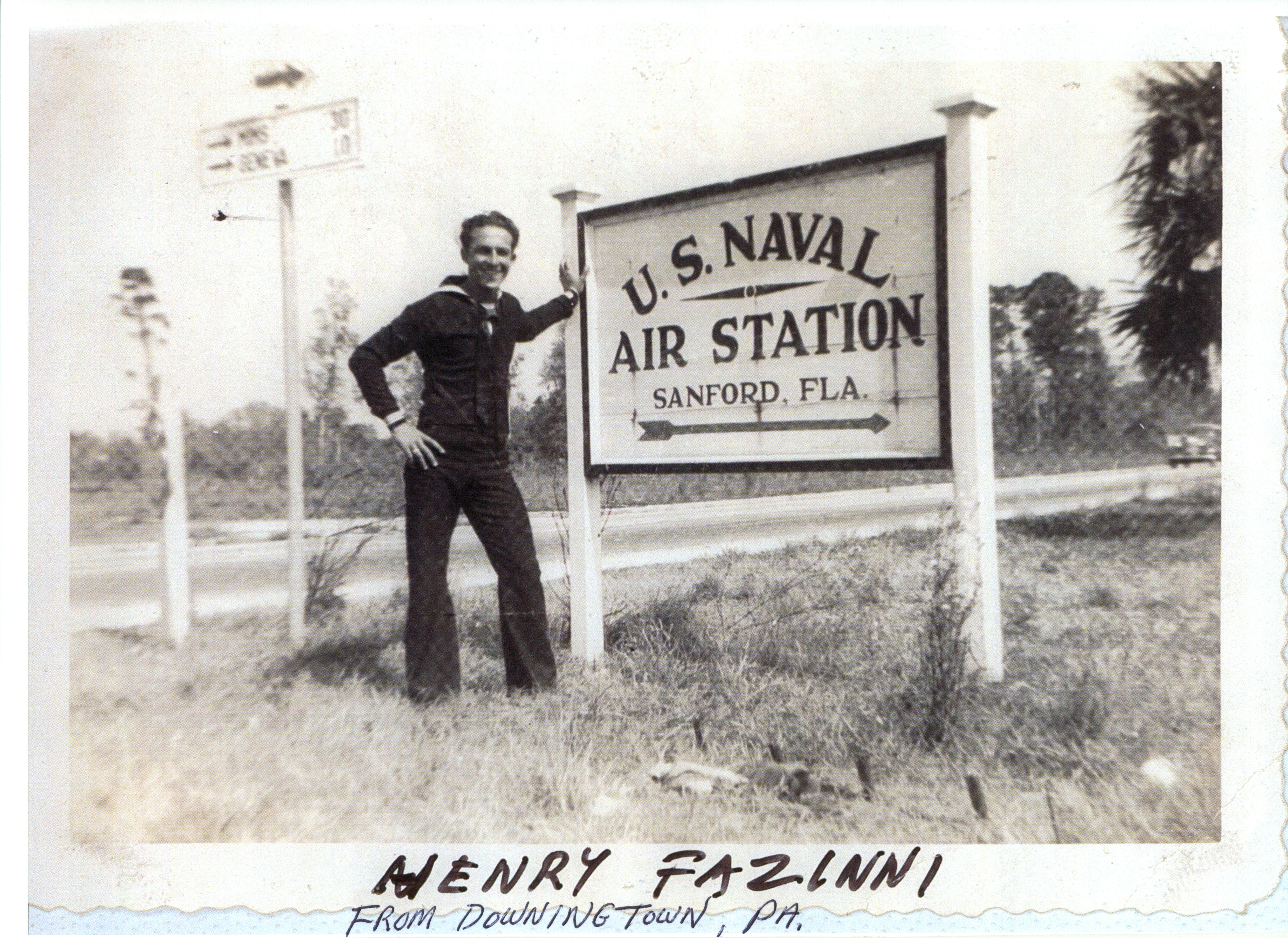 Henry Fazinni, a sailor, next to the sign for the NAS Sanford.