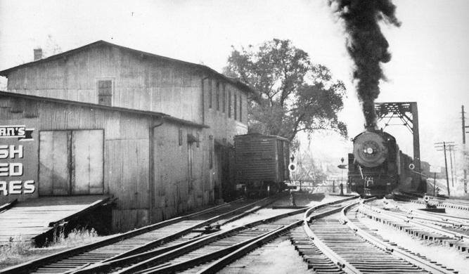 A black and white photo shows the backside of the mill, which abuts railroad tracks.