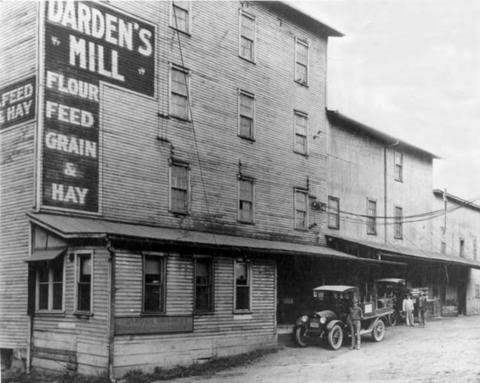 A black and white photo of a four-story building with a historic car parked out front.